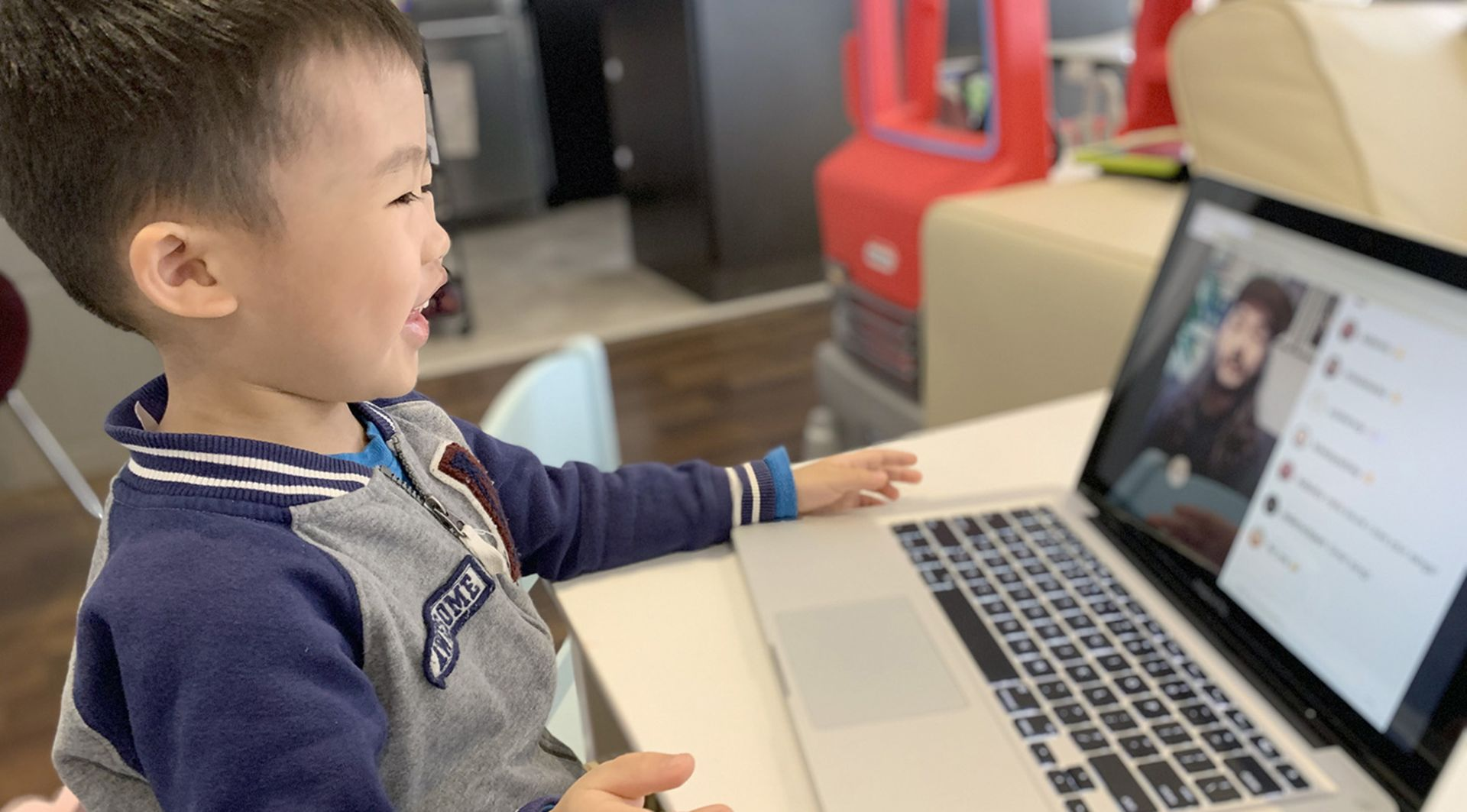 Child looking at a laptop smiling