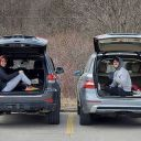 Two people sitting in trunks of their cars at Evergreen Brick Works social distancing.