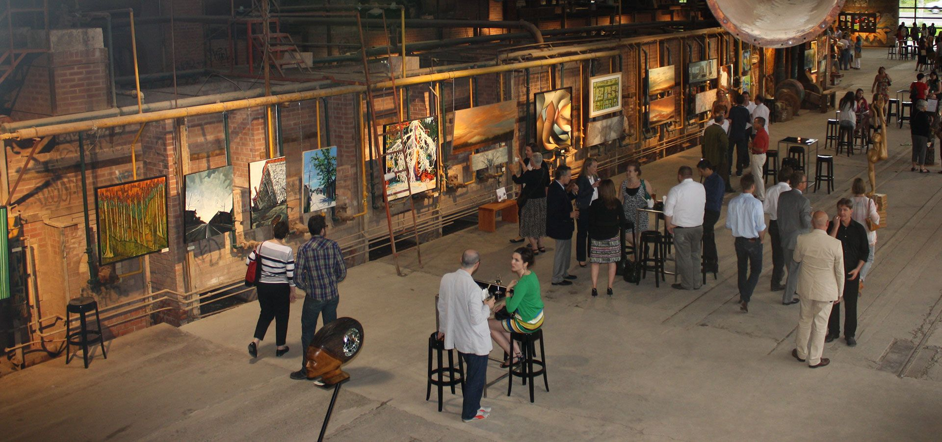 People at an art show in the Kiln Building at Evergreen Brick Works.